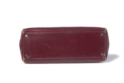 "Hermès ""Kelly"" Hermès ""Kelly""  1957  Cuir bordeau  Garniture métal doré, porté main,..."