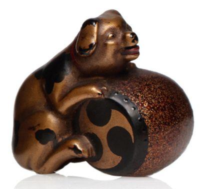 JAPON VERS 1880-1900 Netsuke en bois laqué noir et or, représentant un chiot s'appuyant...