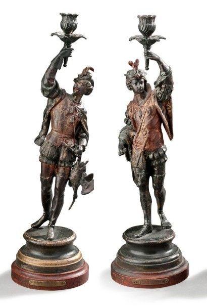 Paire de grands bougeoirs à une lumière en régule représentant deux chasseurs vêtus...
