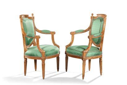 Paire de fauteuils cabriolets en bois mouluré à décor de frises de perles. Dès à...