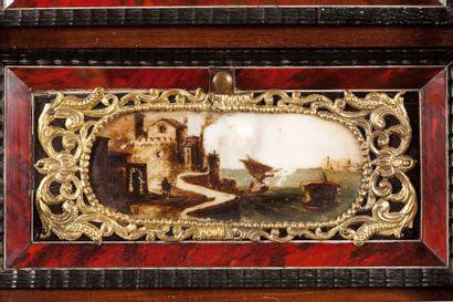 Cabinet en bois noirci et fond d'écailles rouges à décor architecturé agrémenté...