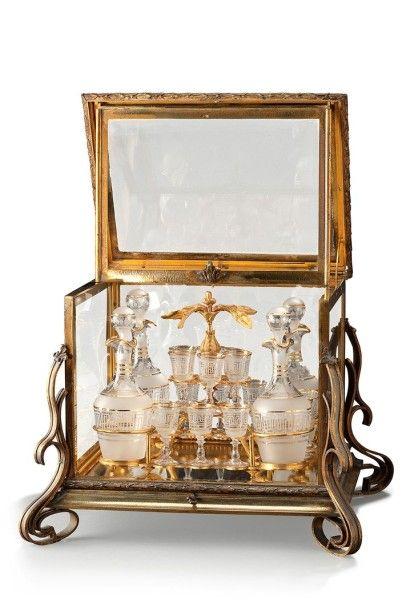 Cave à liqueur en verre et bronze doré à décor de volutes et frises. Elle comprend...