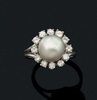 Bague en or gris 18k sertie d'une perle fine dans un entourage de diamants de taille...