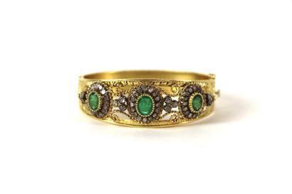 Bracelet manchette en or jaune ciselé et ajouré serti de trois émeraudes ovales...