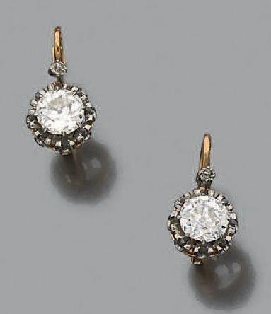 Paire de dormeuses en or jaune et gris 18k (750) serties d'un diamant de taille...