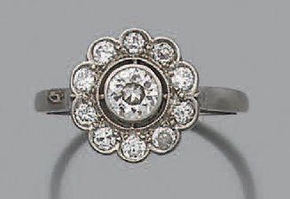 """Bague """"marguerite"""" en PLATINE (950) sertie d'un diamant demi taille dans un entourage..."""