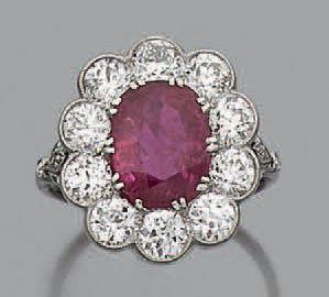 Bague en platine sertie d'un rubis de taille coussin dans un entourage de diamants...