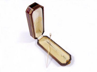 Epingle en or jaune 18k sertie d'une perle fine soutenue d'une fine ligne de diamants...