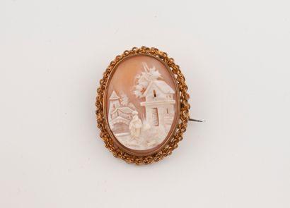 Broche ovale en métal doré centrée d'un camée...