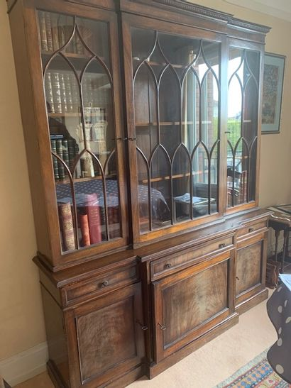 Bookcase with a slight central projection, upper part glazed with arcature deco...