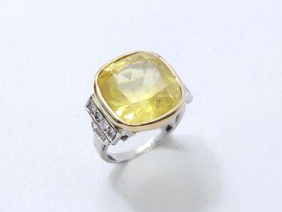 Bague 2 tons d'or 750 millièmes ornée d'un saphir jaune taille coussin en serti...