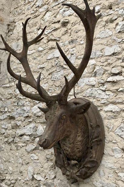 Trophé de cerf à 18 corps.  Posé sur un médaillon ovale à décors de feuilles de...