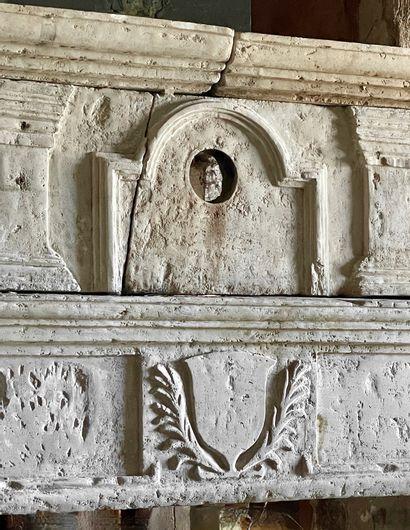 Cheminée Louis 13 en pierre.  Linteau orné d'un écusson central.  Hotte à décor...