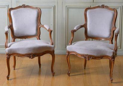 Paire de fauteuils cabriolet en bois naturel mouluré et sculpté de fleurettes. Style...