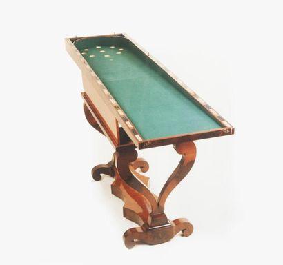 Table à jeux en acajou et placage d'acajou. Le plateau portefeuille garni d'un feutre...