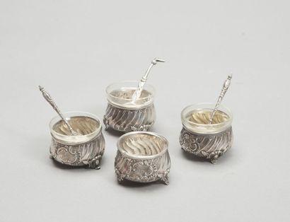 Série de quatre salières rondes en argent à trois pieds, côtes torses et médaillons...