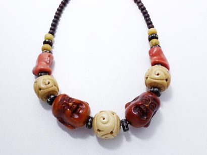Collier composé d'une chute de perles fantaisie en corail teinté, os, bois et matières...