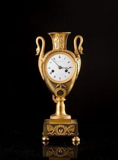 Pendule en bronze ciselé et doré en vase...