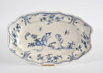 LYON Plat ovale à bords contournés à décor en camaïeu bleu de deux figures grotesques...