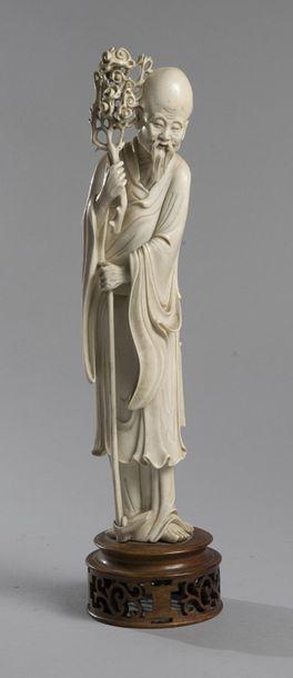 Statuette en ivoire représentant un immortel tenant un ruyi sur un socle bois. Chine,...