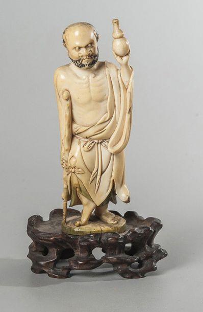 STATUETTE EN IVOIRE représentant un personnage debout appuyé sur une canne et portant...