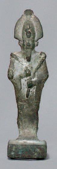 Statuette d'OSIRIS momiforme debout portant le sceptre et le flagellum. Il repose...
