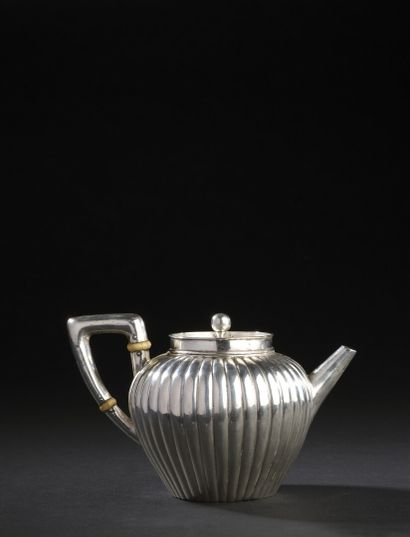 Silver teapot with gadrooned ribs, the handle...