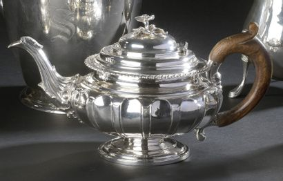 Silver teapot, circular in shape, resting...