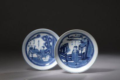Deux assiettes en porcelaine blanc bleu à décor de scènes de la vie quotidienne,...