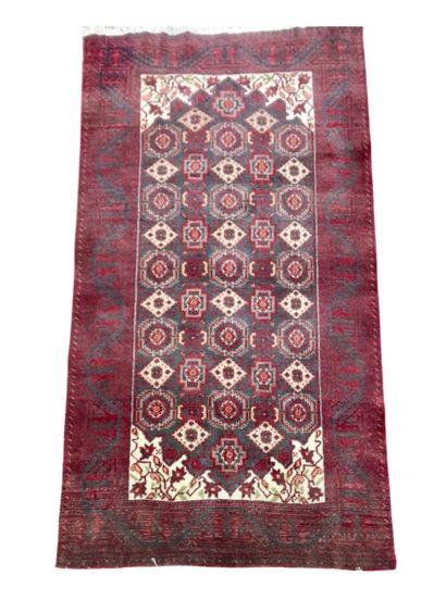 Tapis Afghanà motifs géométriques sur fond...