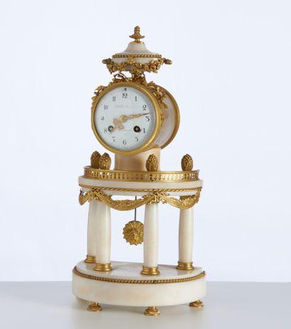 Une pendule portique demi-lune en marbre blanc et bronze doré de style Louis XVI....