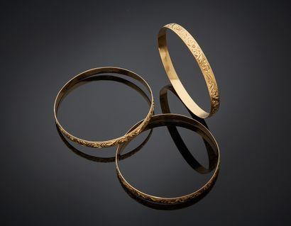 Trois BRACELETS rigides en or rose (750)...