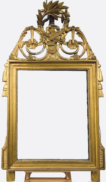 Miroir en bois doré à fronton ajouré de feuillages,...