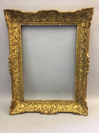 *Cadre en bois et stuc doré à décor Bérain....
