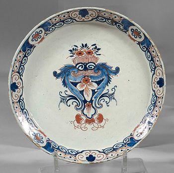 DELFT Trois assiettes et un plat en faïence à décor en bleu et rouge de panier fleuri...
