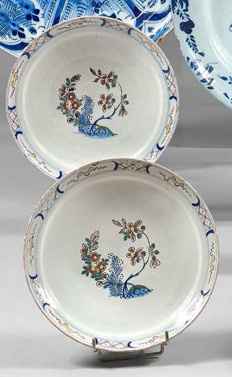 DELFT Pair of earthenware plates with polychrome decoration of flowers, the border...