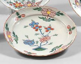 DELFT Suite of three earthenware plates with polychrome decoration of flowers. Blue...