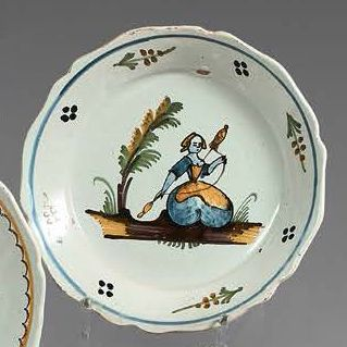 NEVERS Four earthenware plates, three of which have contoured edges, with different...