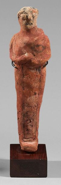 Shaouabti inscribed on a ventral column. The arms and eyes are shaped. Ochre terracotta...