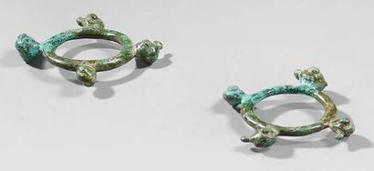 Pair of rings decorated with four zoomorphic heads with bulging eyes. Bronze with...