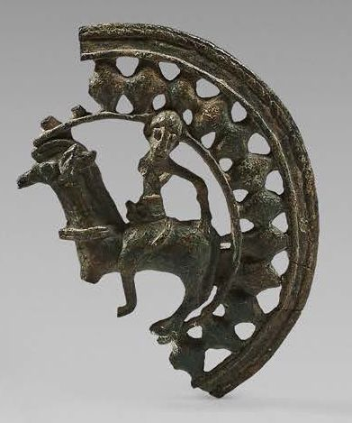 Piece of an openwork circular belt buckle with a rider motif passing to the left....