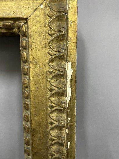 Paire de cadres en bois sculpté et doré à décor de pastilles en fronton et feuiles...