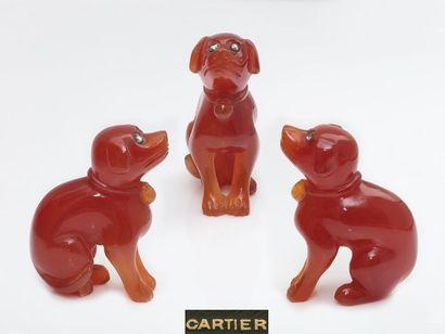 CARTIER. Petit chien assis en cornaline, les yeux ponctués de roses couronnées en...