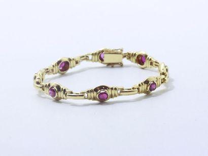 Bracelet articulé en or 750 millièmes, composé de maillons centrés de rubis ovales...