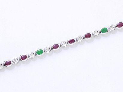 Bracelet souple en or gris 750 millièmes, composé d'une ligne de rubis et d'émeraudes...