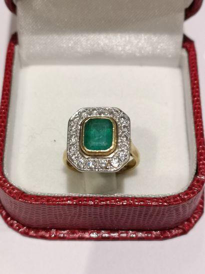 Bague en or 750°/°° ornée d'une émeraude dans un entourage diamanté.  Poids brut...