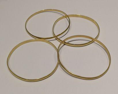 Quatre bracelets joncs en or 750°/°°, les...