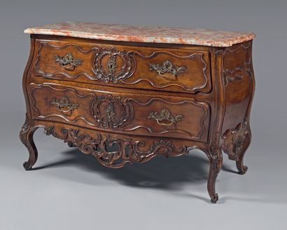 A walnut chest of drawers, moulded and carved...