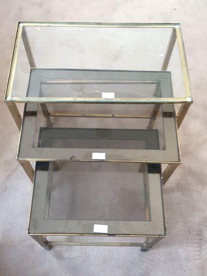 Trois tables gigognes en métal doré et verre....