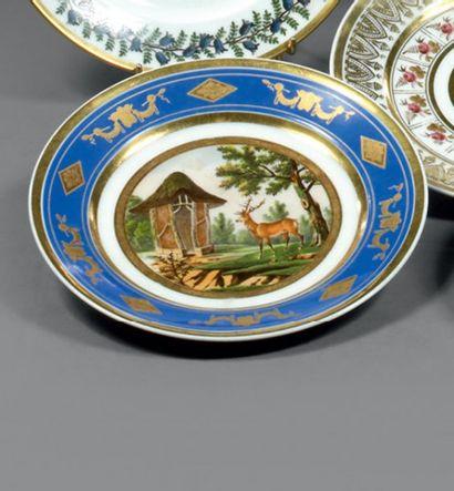 PARIS. Assiette ronde décorée en polychromie dans un médaillon central d'un cerf...